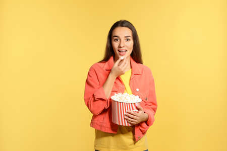 Woman with popcorn during cinema show on color background