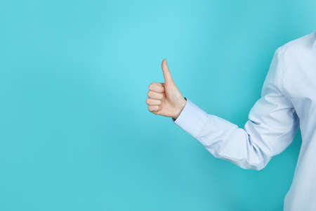Young woman showing thumb sign on color background. Space for text Stock Photo