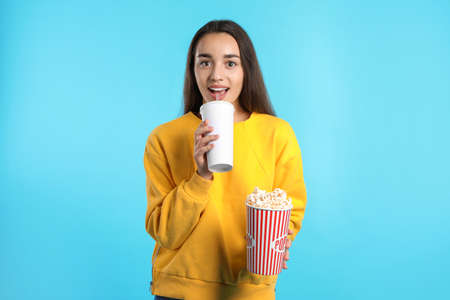 Woman with popcorn and beverage during cinema show on color background