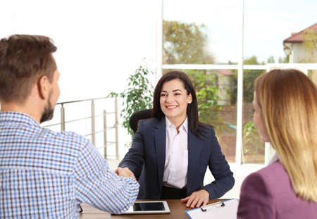 Human resources manager shaking hands with applicant during job interview in office