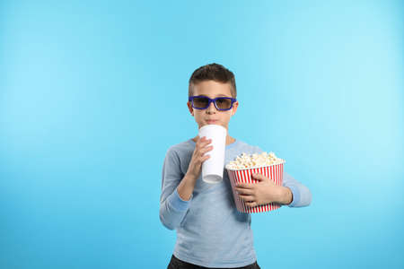Boy with 3D glasses, popcorn and beverage during cinema show on color background