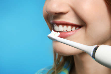 Young woman with electric toothbrush on color background, closeup. Space for text