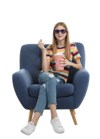 Teenage girl with 3D glasses and popcorn sitting in armchair during cinema show on white background Stock Photo