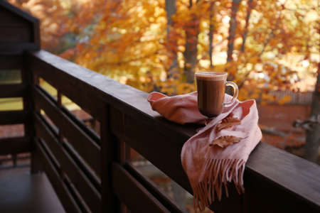 Hot cozy drink and warm scarf on wooden railing at balcony. Space for text