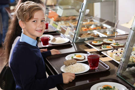 Cute boy near serving line with healthy food in school canteen Stockfoto