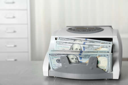 Modern bill counter with money on table indoors Stock Photo