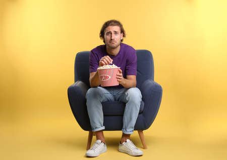 Emotional man with popcorn sitting in armchair during cinema show on color background Stock Photo