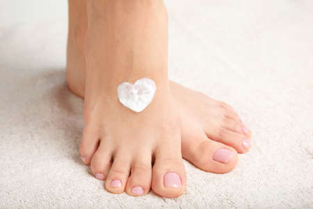 Woman with cream on her foot, closeup. Spa treatment