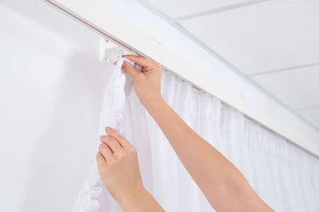 Woman hanging window curtain indoors, closeup. Interior decor element