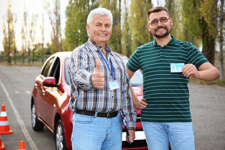 Senior instructor and happy man with driving license outdoors