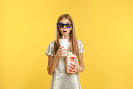 Emotional teenage girl with 3D glasses, popcorn and beverage during cinema show on color background Stock Photo