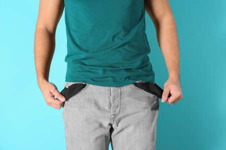 Man showing empty pockets on color background, closeup Banco de Imagens