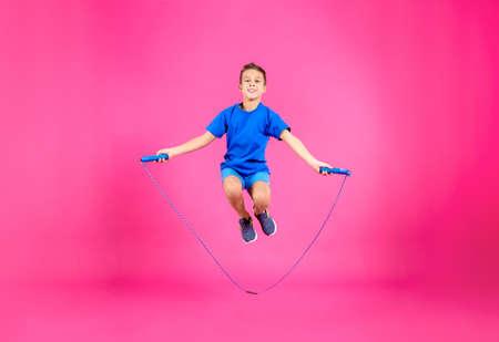 Retrato de cuerpo entero de niño saltando la cuerda sobre fondo de color