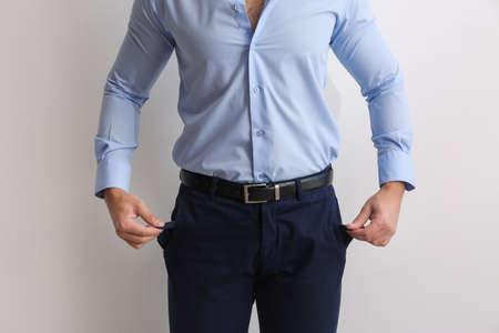 Businessman showing empty pockets on light background, closeup