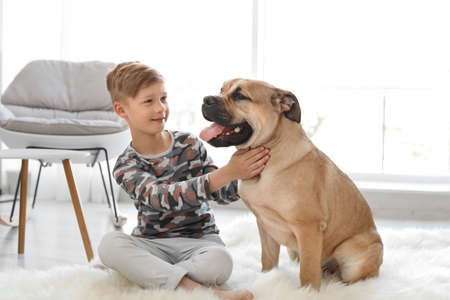 Cute little child with his dog at home