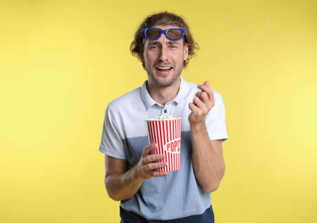 Emotional man with 3D glasses and popcorn during cinema show on color background