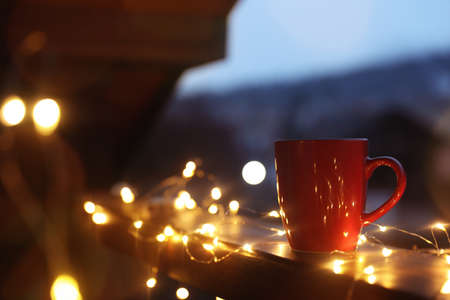 Cup of hot beverage on balcony railing decorated with Christmas lights, space for text. Winter evening 免版税图像