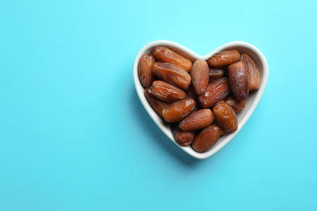 Heart shaped bowl with sweet dried date fruits on color background, top view. Space for text Stock Photo
