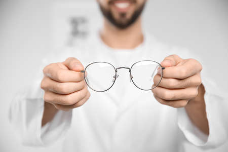 Male ophthalmologist with eyeglasses in clinic, closeup