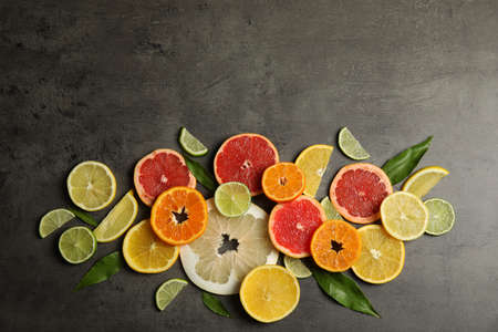 Different citrus fruits on grey background, top view. Space for text