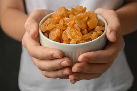 Woman holding bowl with raisins on black background, closeup 免版税图像