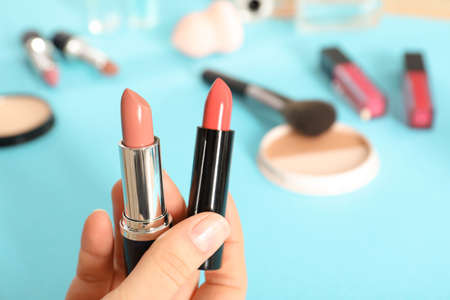 Woman holding different lipsticks over color table, closeup. Space for text