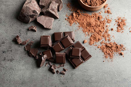 Pieces of chocolate and cocoa powder on grey background, flat lay