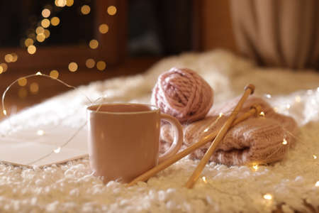 Composition with cup of hot beverage, knitting yarn and book on fuzzy rug. Winter evening Stock Photo