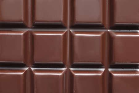 Tasty dark chocolate bar as background, top view
