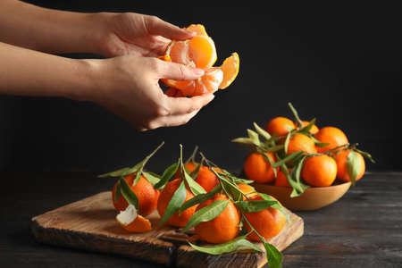 Woman peeling ripe tangerine over table on dark background, closeup