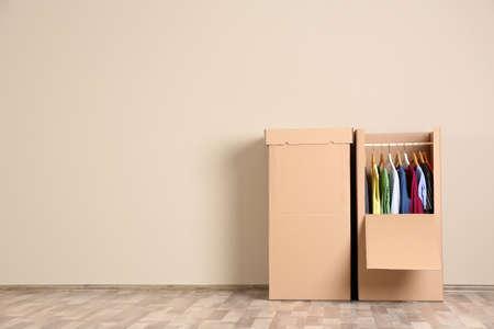Boîtes de garde-robe avec des vêtements contre un mur de couleur à l'intérieur. Espace pour le texte