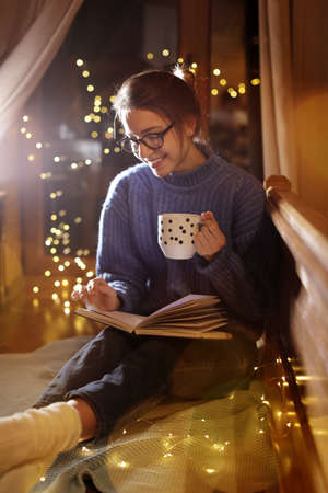 Woman with cup of hot beverage reading book at home in winter evening