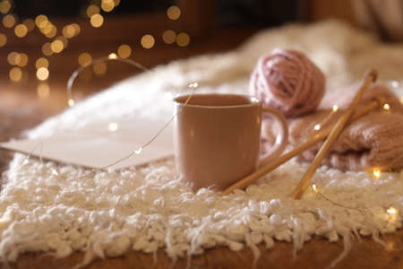 Composition with cup of hot beverage, knitting yarn and book on fuzzy rug. Winter evening Reklamní fotografie