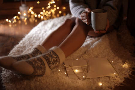 Woman with cup of hot beverage and book at home in winter evening, closeup