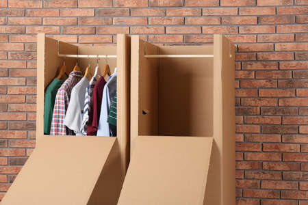 Wardrobe boxes with clothes against brick wall