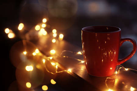 Cup of hot beverage on balcony railing decorated with Christmas lights, space for text. Winter evening Stock Photo