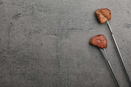 Forks with fried meat fondue pieces on grey background, top view. Space for text