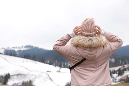 Young woman in warm clothes near snowy hill, space for text. Winter vacation