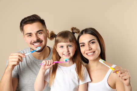 Little girl and her parents brushing teeth together on color background