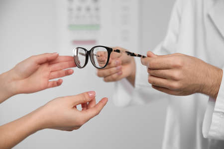 Male ophthalmologist helping woman choose glasses in clinic, closeup Foto de archivo