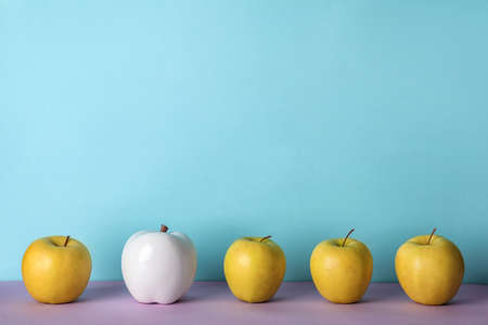 Row of fresh apples with decorative one on color background. Be different