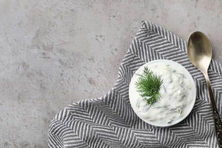 Cucumber sauce, spoon and space for text on grey background, flat lay. Traditional Tzatziki