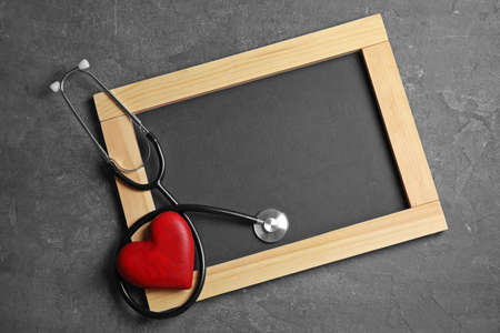 Stethoscope, heart and blackboard with space for text on gray background, top view. Cardiology concept