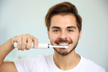 Portrait of young man with electric toothbrush on blurred background