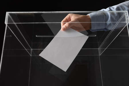 Man putting his vote into ballot box on black background, closeup