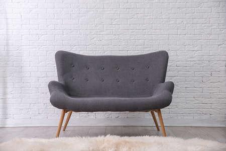 Simple living room interior with comfortable sofa near brick wall