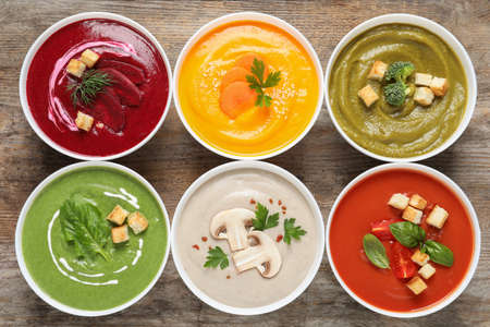 Various cream soups in bowls on wooden background, top view