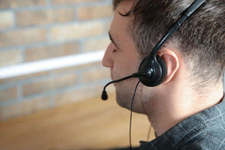 Male technical support operator with headset at workplace Imagens