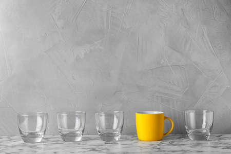 Rangée de verres avec tasse lumineuse sur table. Sois différent