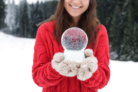 Woman with knitted mittens holding snow globe outdoors, closeup. Winter vacation